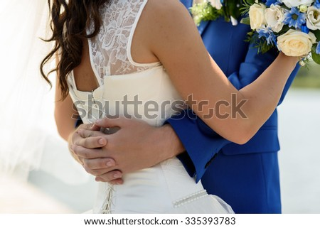 groom in a blue suit hugs the bride's waist