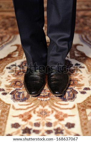 groom in black shoes standing on carpet at home