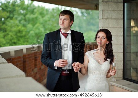 Groom in black tuxedo holds bride's hand while they walk along the balcony