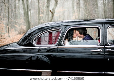 Groom in dark blue jacket leans to bride for a kiss while sitting in the car