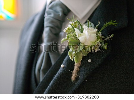Groom in suit with white rose button hole flower close up