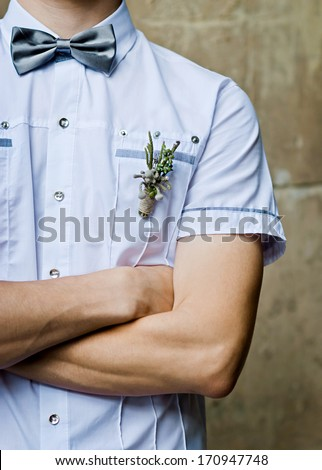Groom in white shirt and bow tie his arms folded (partial)  - stock photo