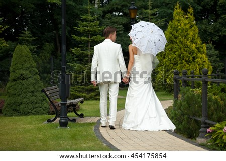 Groom in white suit holds bride's hand while walking in the garden