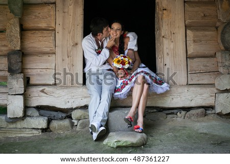 Groom in white suit kisses bride's cheek tender while they sit on the wooden footstep