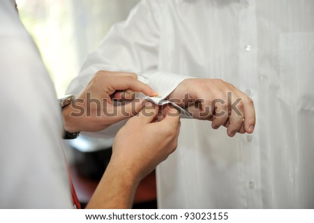Groom is buttoning his sleeve link with a help of a friend - stock photo
