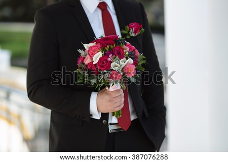 Groom is holding wedding bouquet with red roses