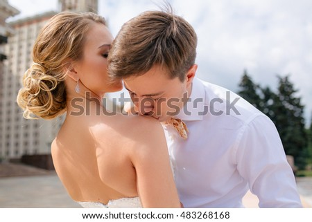 Groom is kissing a shoulder of his bride