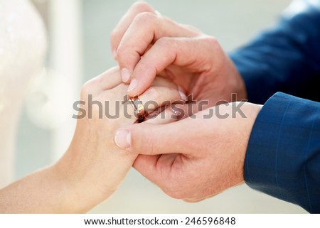 Groom is putting on a ring on bride's finger - stock photo