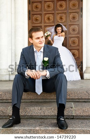 Groom is sitting near the church and thinking about future. His bride with the flowers on the background.