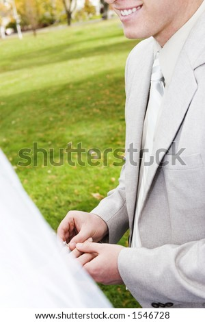 Groom is smiling as he places wedding ring onto brides finger in the middle of beautiful park