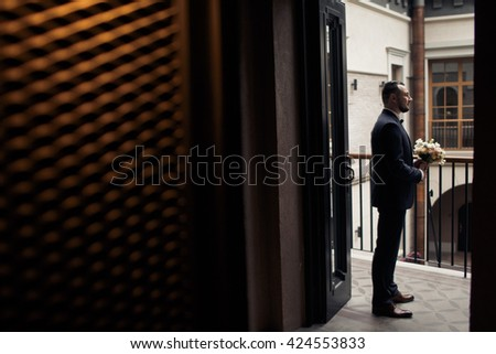 Groom is waiting for the bride with flowers