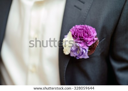 Groom is wearing a boutonniere indoors. Male portrait of handsome guy. Beautiful model boy in colorful wedding clothes. Man is posing - stock photo
