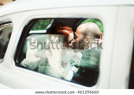 Groom kisses a bride behind a steamy car window