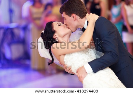 Groom kisses a bride bending her over during their first dance - stock photo