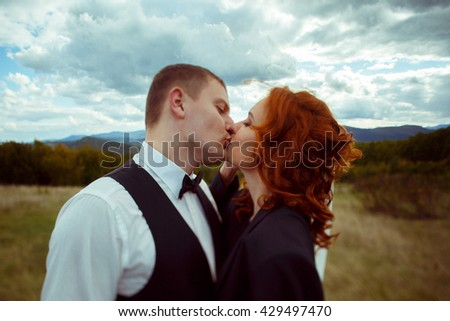 Groom kisses a bride with curly red hair dressed in his jacket
