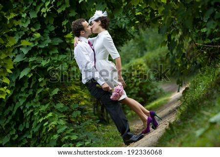 Groom kisses bride. Couple in a garden. Wedding theme.  - stock photo