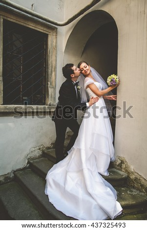Groom kisses bride's cheek bending her over in the entrance