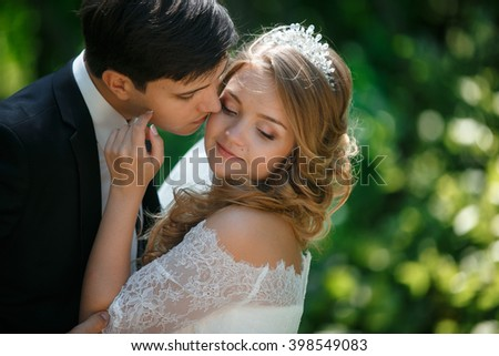 Groom kisses his bride to the cheek