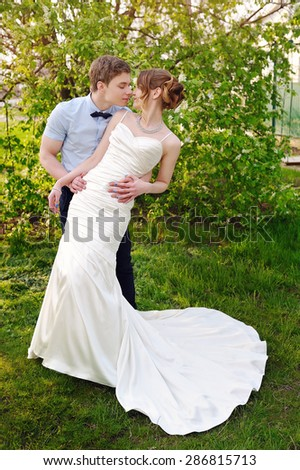 groom kisses the bride on walk on their wedding day.