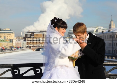 groom kissing bride hand at winter outdoors, couple standing on bridge - stock photo