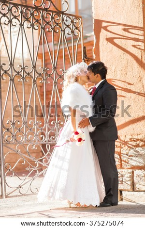 Groom kissing bride on their wedding day