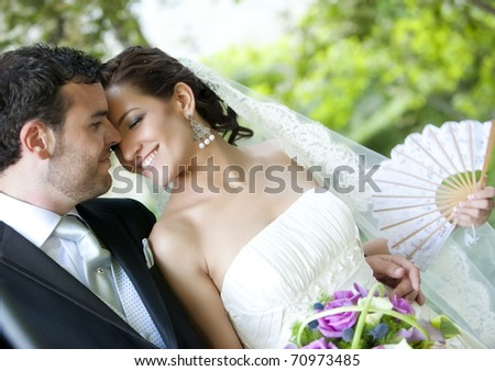 Groom kissing bride on their wedding day.