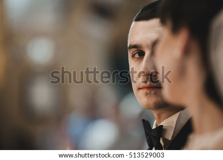 Groom looks at a bride on the wedding ceremony