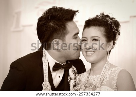 groom lovingly kissing his biracial bride on her cheek ,thai wedding culture