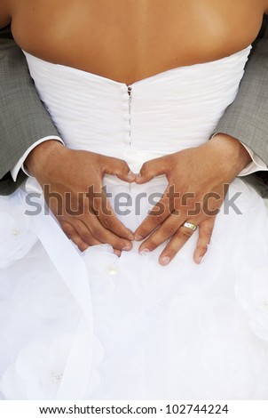 Groom making a heart sign while his arms are around his bride.