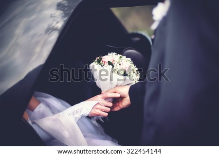 Groom meets the bride from the car with a wedding bouquet of flowers - stock photo