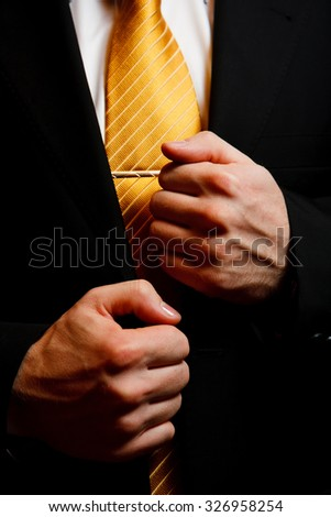 Groom on wedding day morning clothing - man's black suit with yellow tie and hands closeup - stock photo