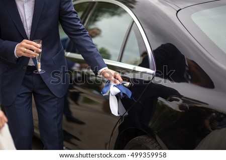 Groom opening the luxury wedding car doors for the bride