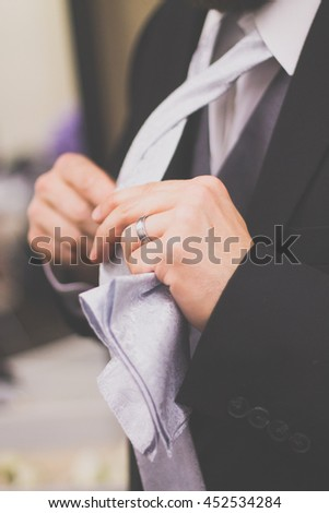 Groom or man adjusting tie on wedding day - stock photo
