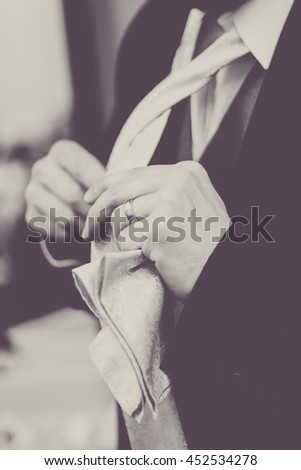 Groom or man adjusting tie on wedding day vintage black and white. - stock photo