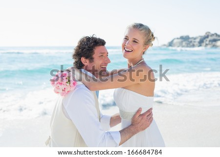Groom picking up his pretty new wife at the beach