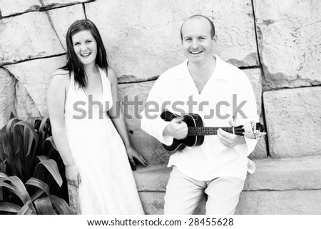 Groom playing the guitar to his new bride - black and white image.