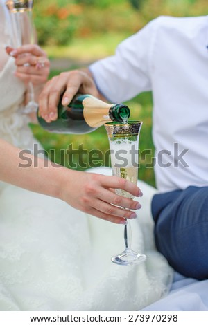 groom pouring for bride champagne into the glass in the summer park. - stock photo