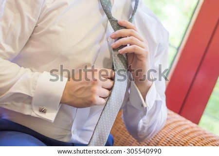 Groom prepares for the wedding, he's putting up his tie - stock photo
