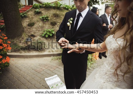 Groom puts a wedding ring on bride's finger while they stand on the wedding towel