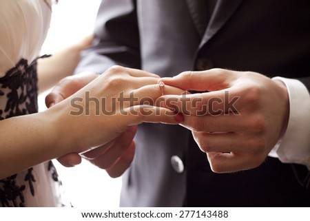 Groom putting a wedding ring on the finger of the bride - stock photo