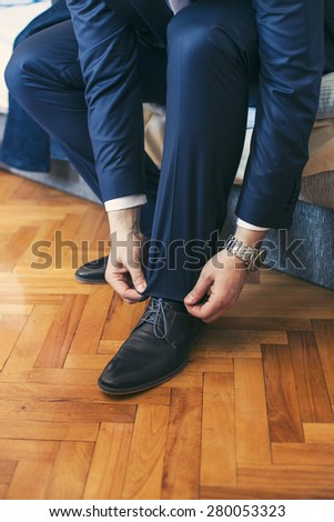 Groom putting his wedding shoes