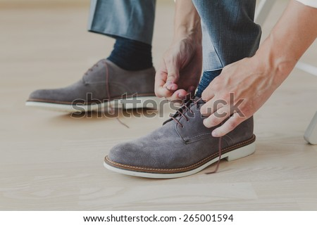 groom putting his wedding shoes. Hands of wedding groom getting ready - stock photo