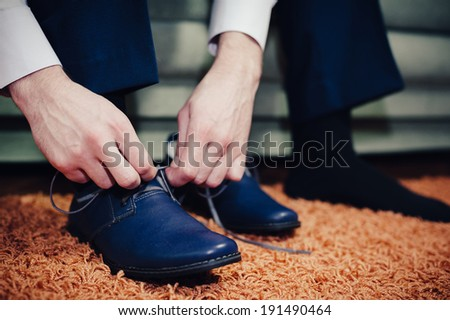 groom putting his wedding shoes. Hands of wedding groom getting ready in suit - stock photo