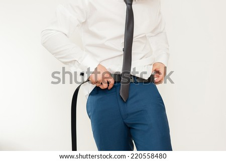 Groom putting on belt as he gets dressed in formal wear .Groom's suit - stock photo