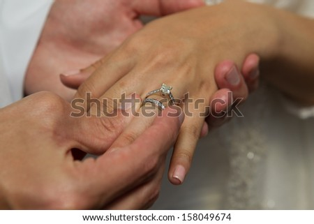 groom putting on brides wedding ring on their wedding day - stock photo