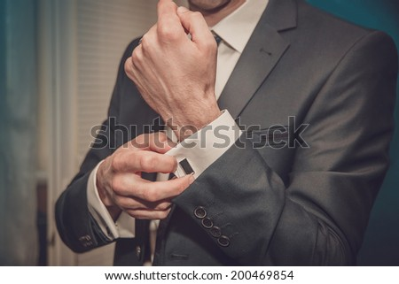 groom putting on cuff-links as he gets dressed in formal wear close up - stock photo