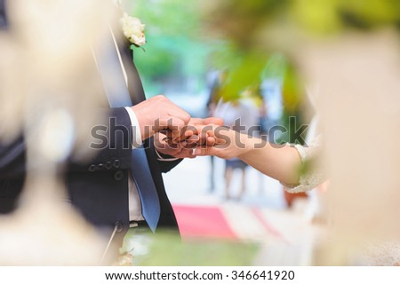groom putting on ring on bride's finger