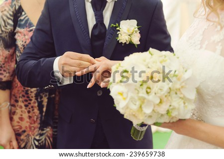 groom putting on wedding ring on bride's finger - stock photo