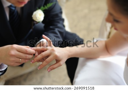 Groom putting ring on bride's finger - stock photo