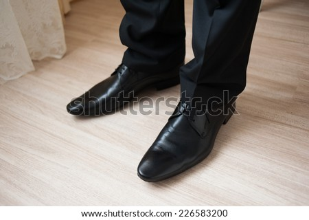 Groom's feet with wedding shoes on - stock photo